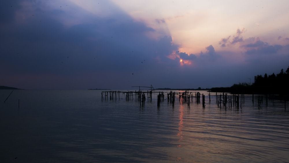 dock under cloudy sky during daytime