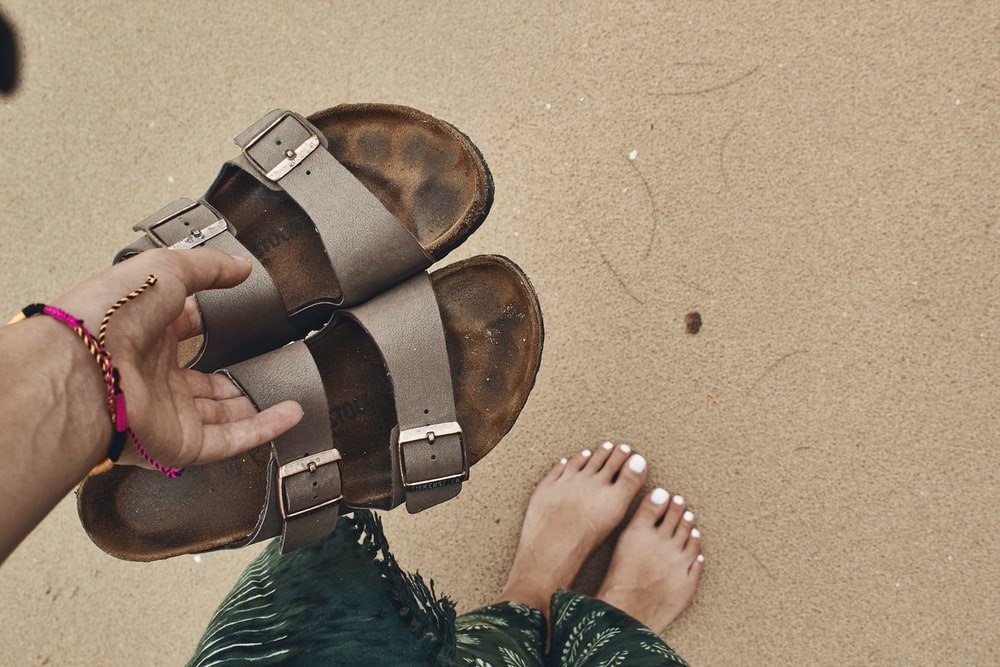 person holding pair of brown-and-black open toe sandals