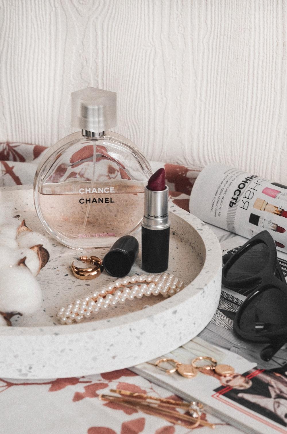 Chanel perfume bottle beside maroon lipstick