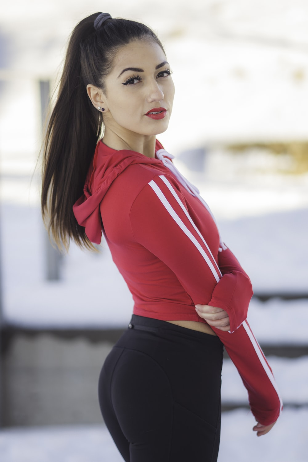 woman in red and white hoodie posing