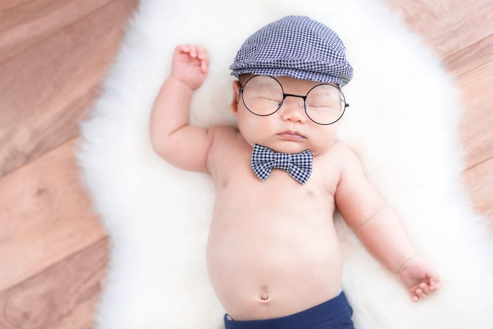 topless baby with beret lying on white fleece rug
