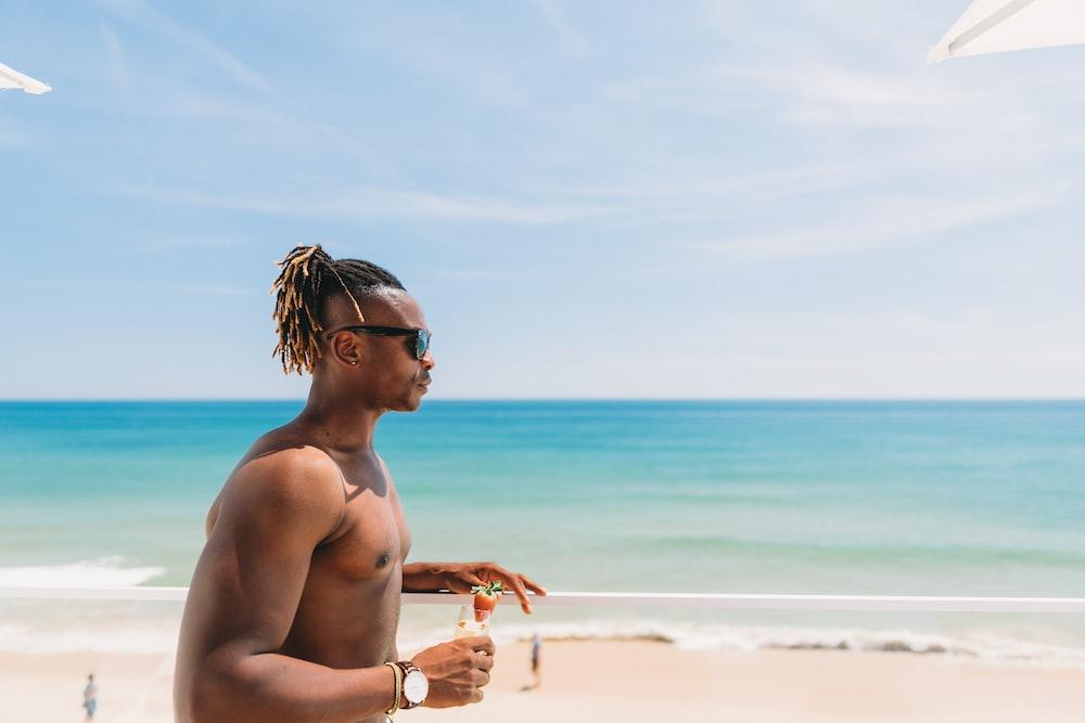 topless man wearing sunglasses standing near seashore
