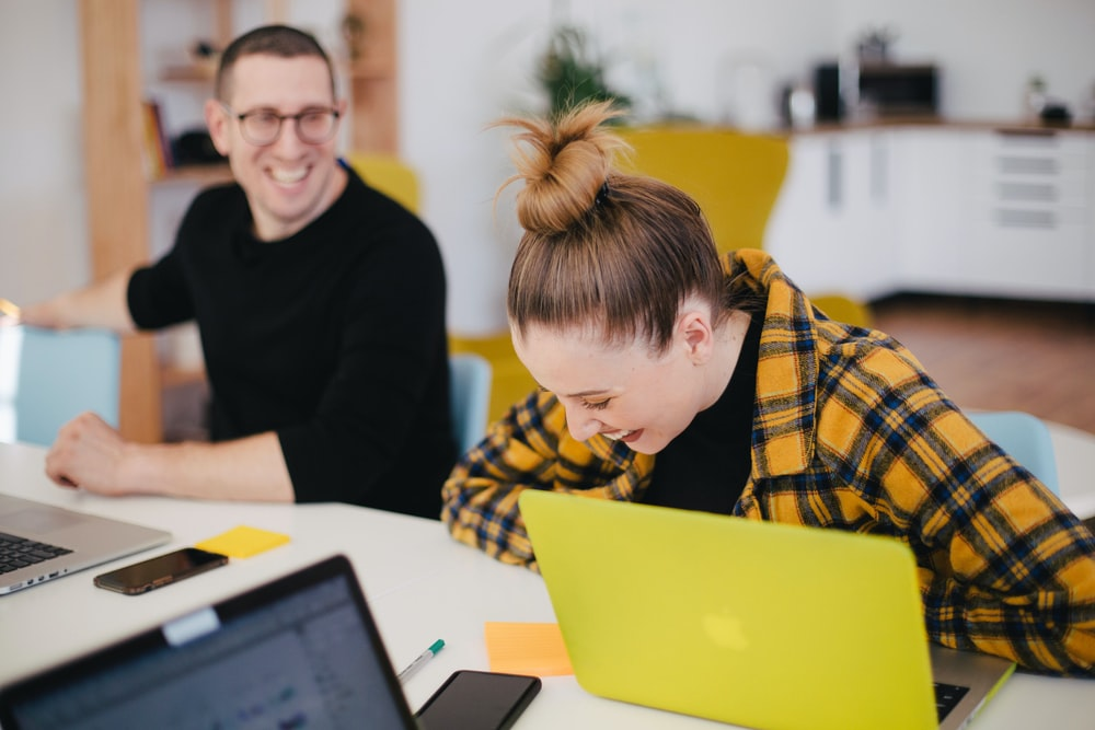 man and woman laughing while sitting in front of laptops