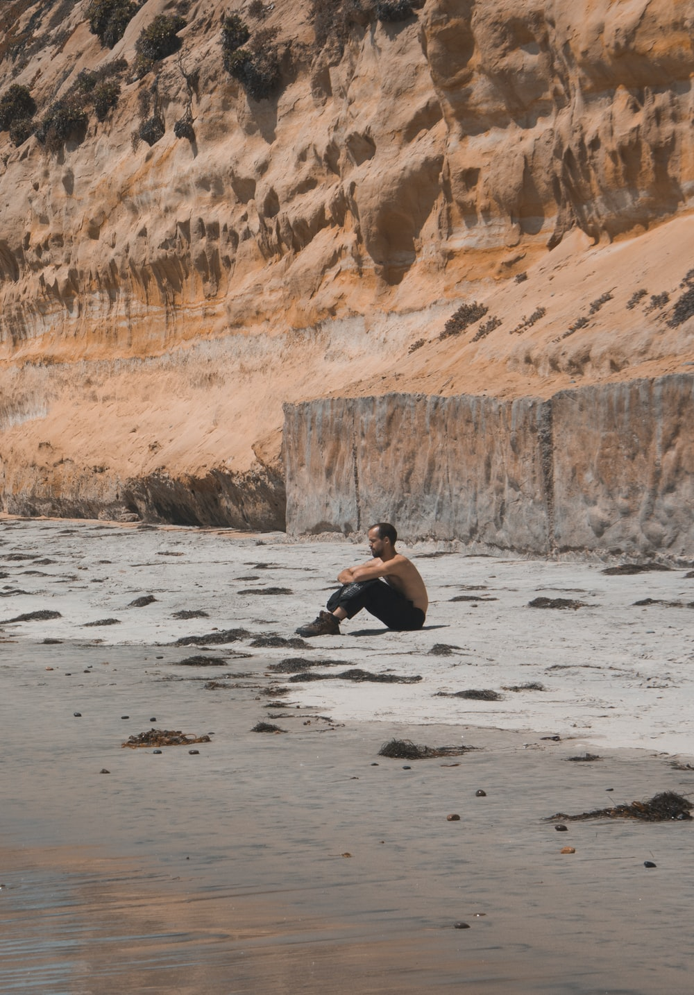 man sitting on shore during day