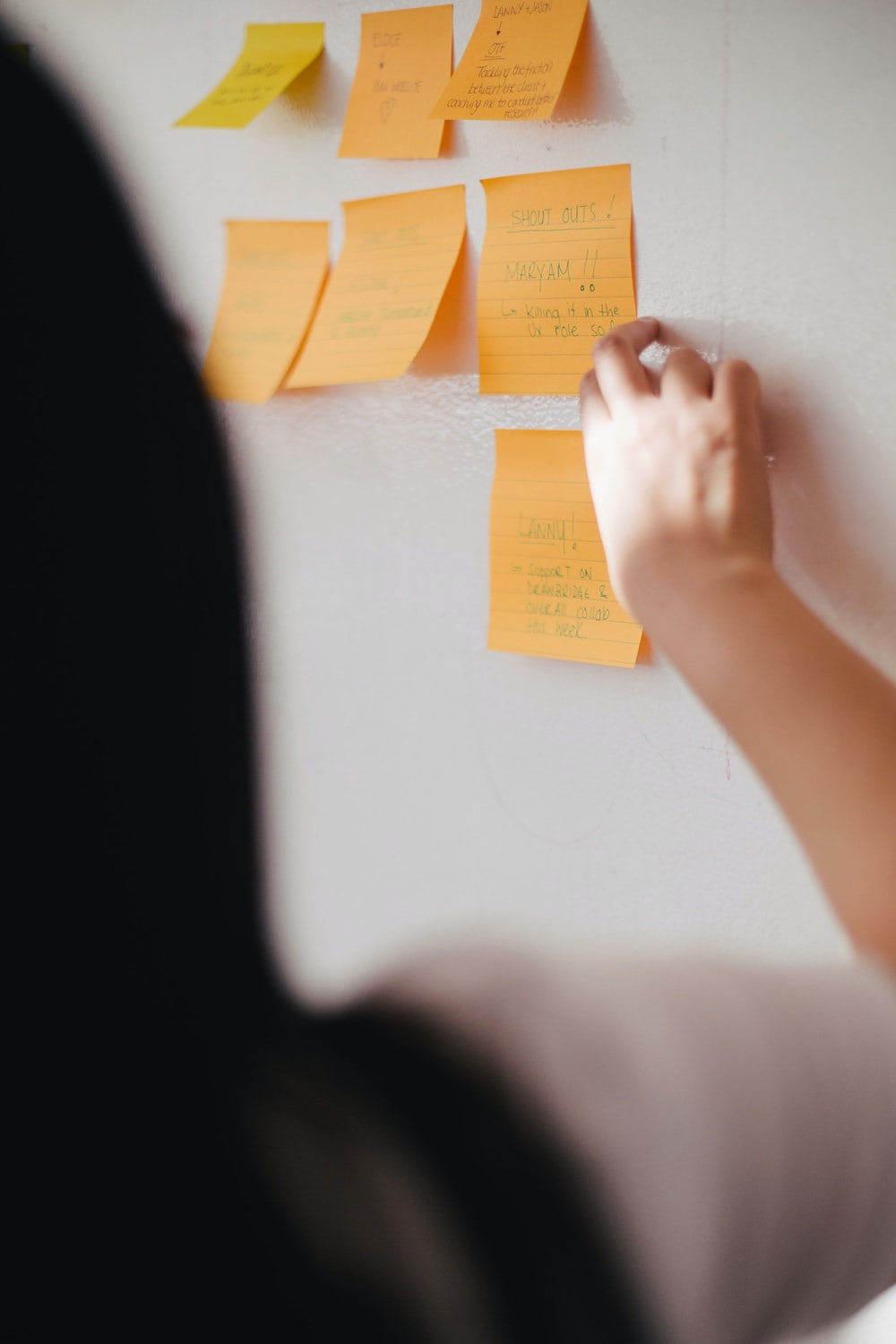 woman putting orange sticky notes on wall
