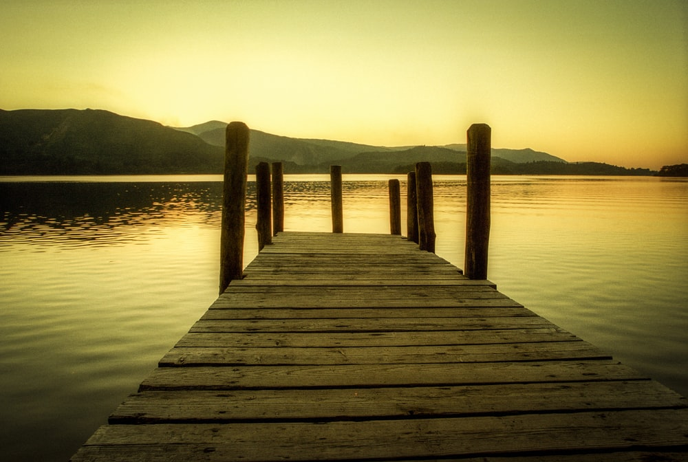 brown wooden dock at the lake during sunset