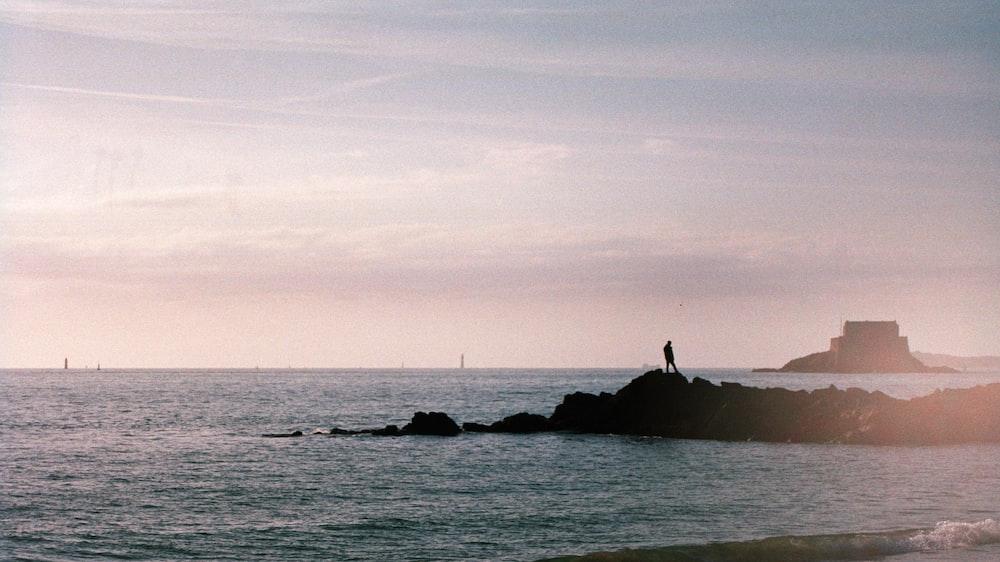 person standing on rock near ocean