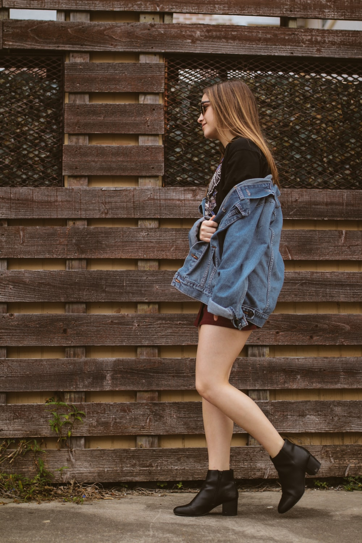woman walking near brown wall