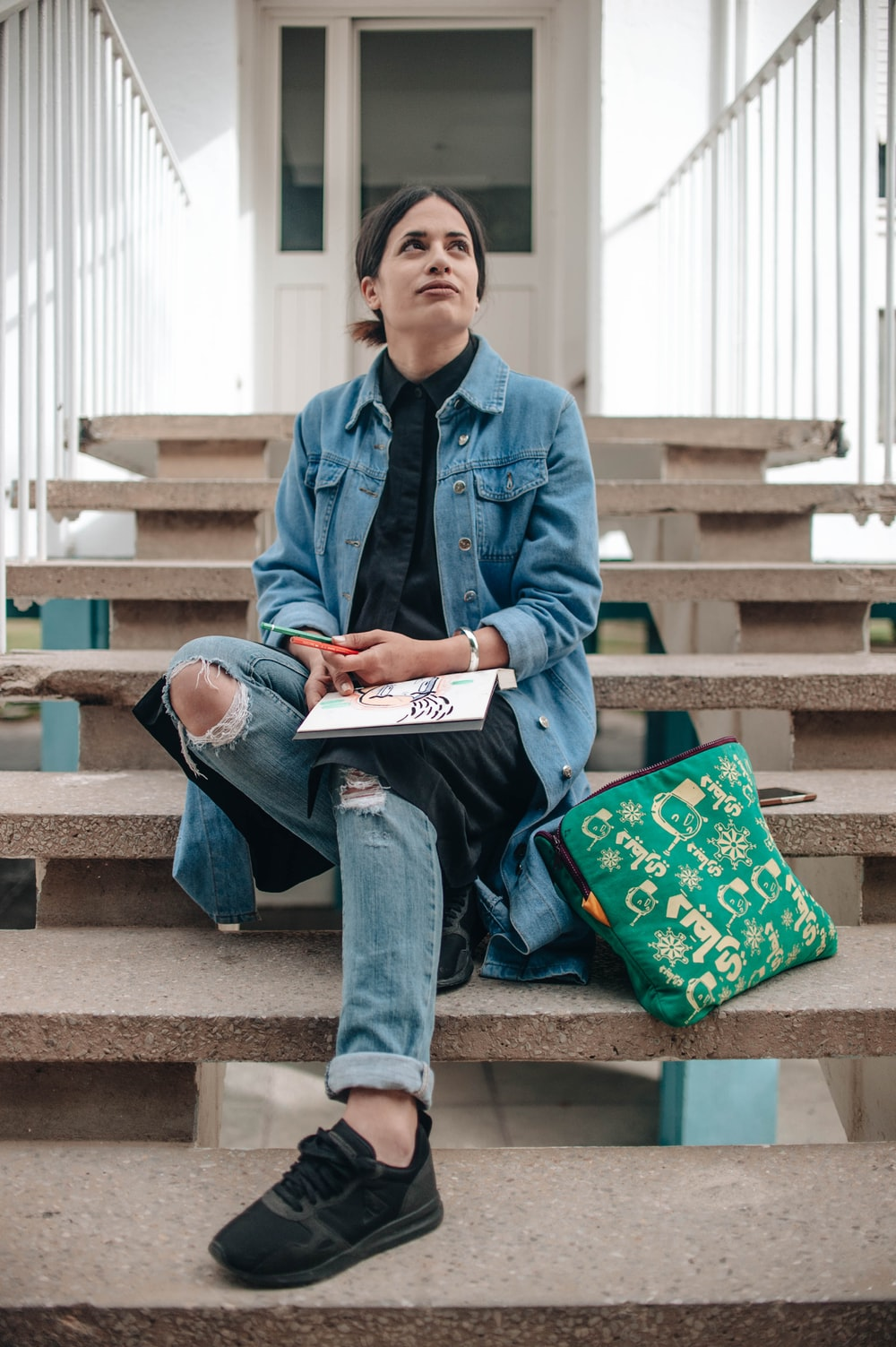 woman sitting on concrete stair with book on lap