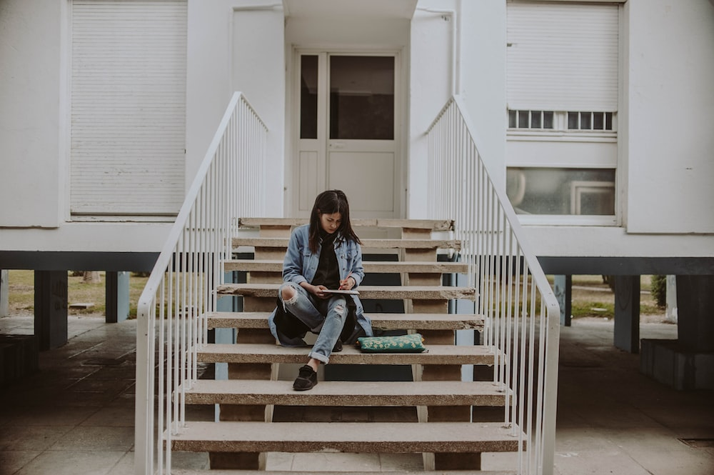 woman sitting on stair while holding book