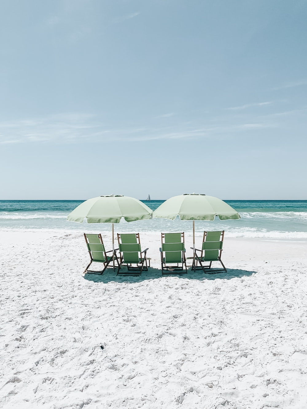 green chairs under umbrellas on shore