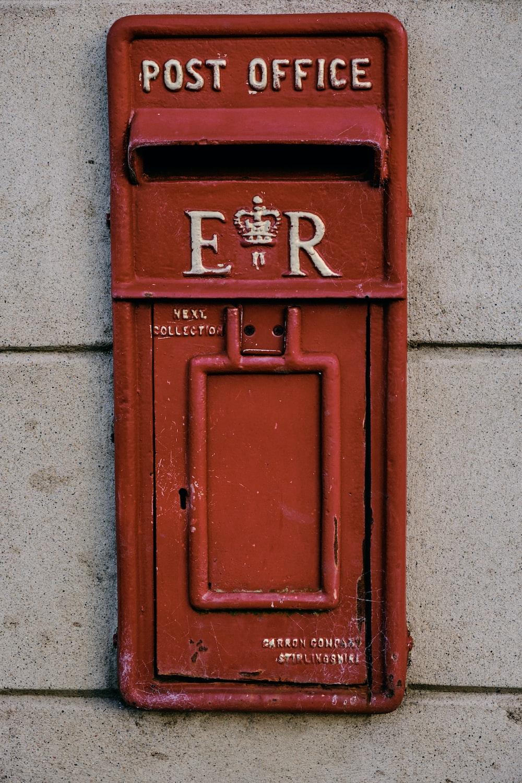 orange post-office mail box on wall