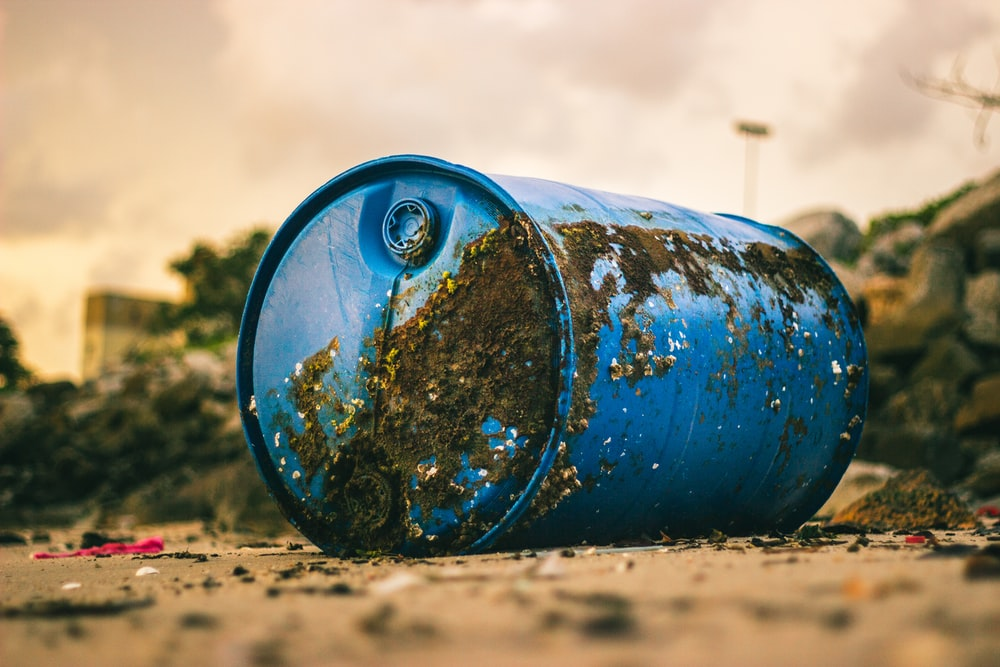 blue plastic barrel with mud on the ground
