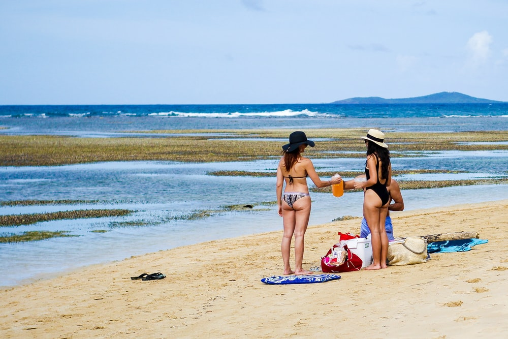 man and two women at shore during daytime