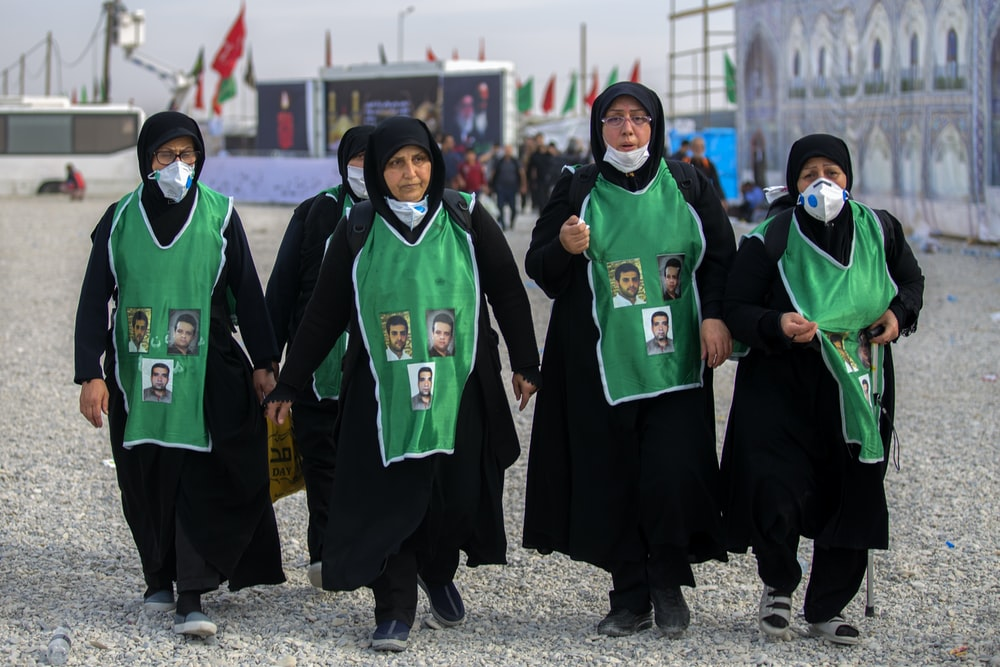 group of women wearing black and green abaya dresses