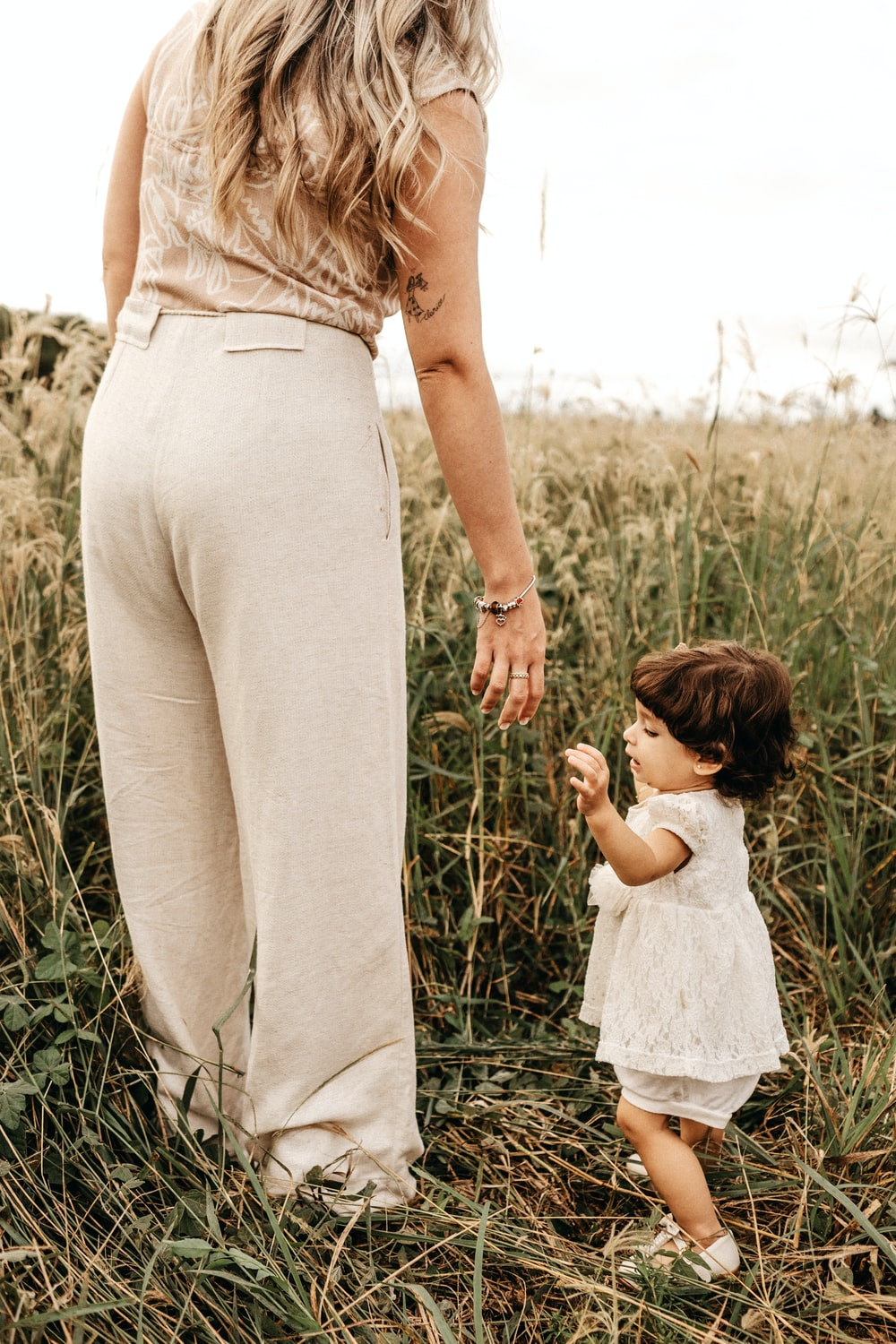 woman standing beside girl during daytime