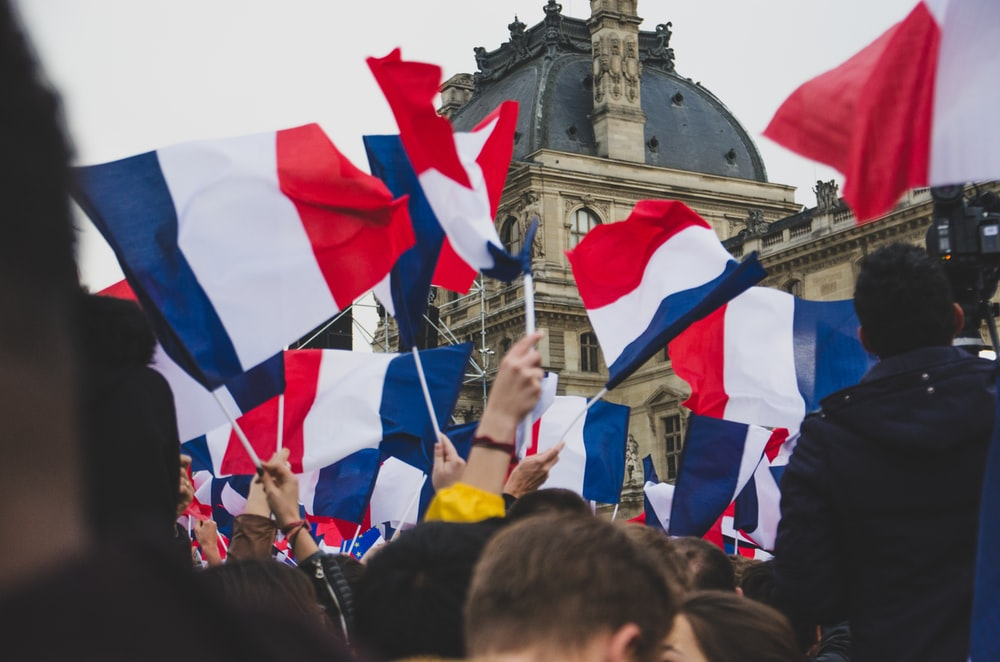 people holding France flag in the street