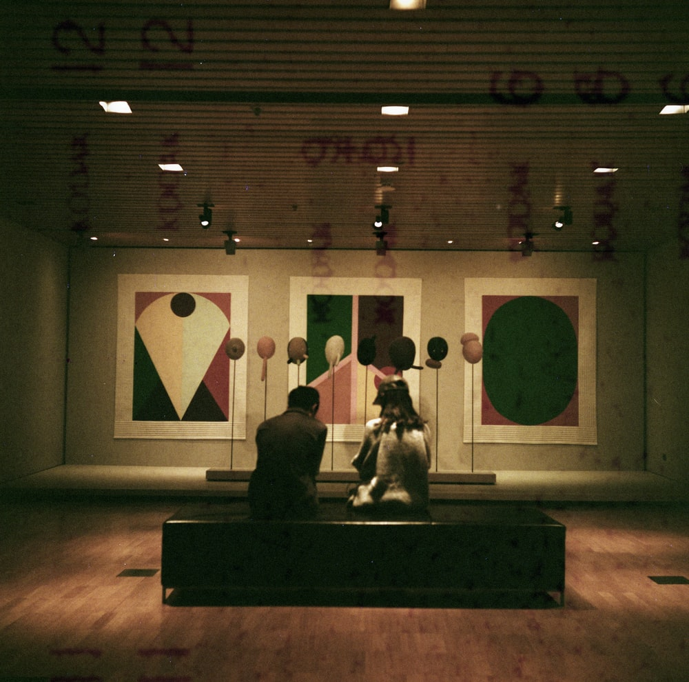 man and woman sitting in front of paintings