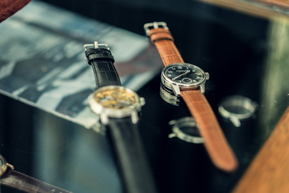 shallow focus photo of two round silver-colored watches