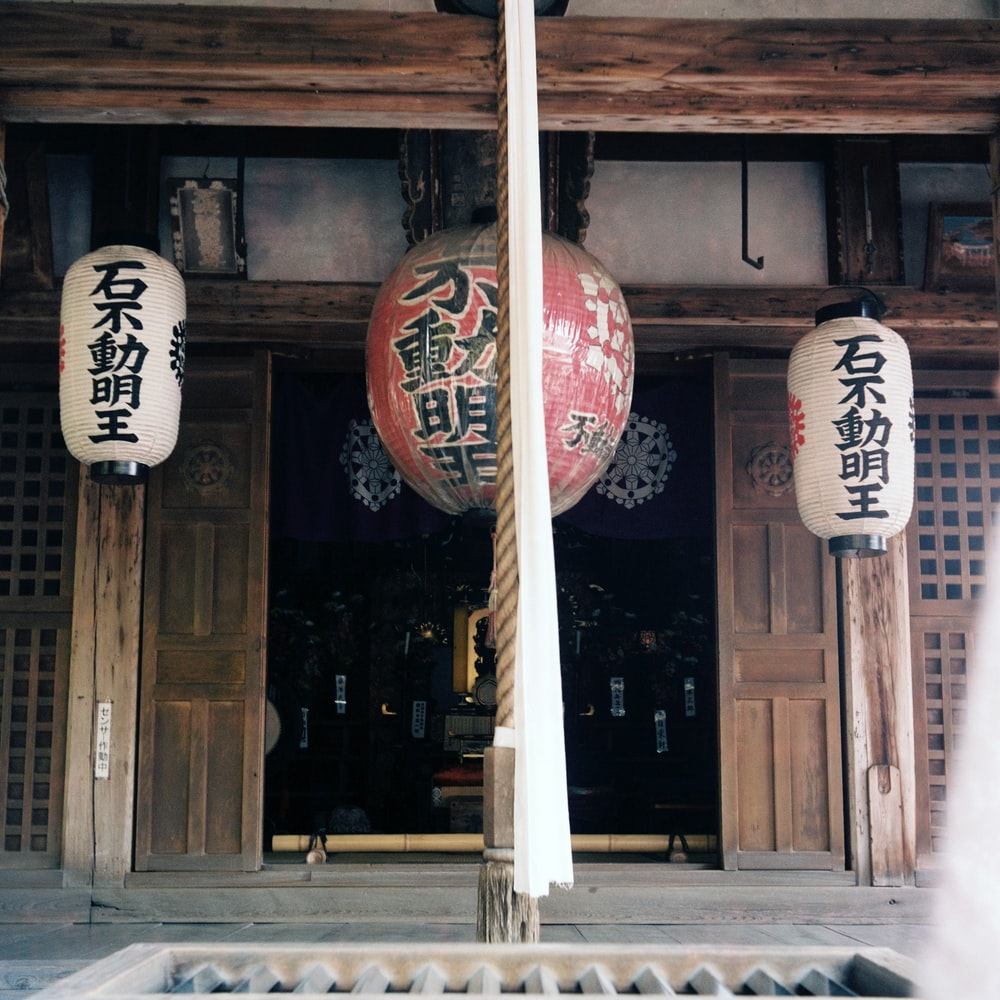 three hung red and white lanterns with kanji prints in front of opened door