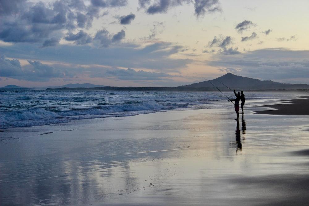 two people holding fish reels on seashore