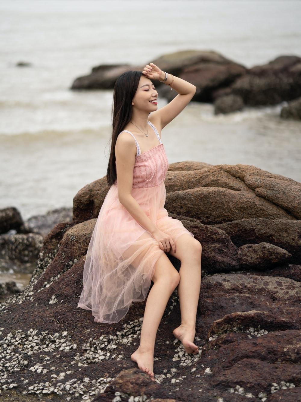 woman in pink dress sitting on seaside rocks