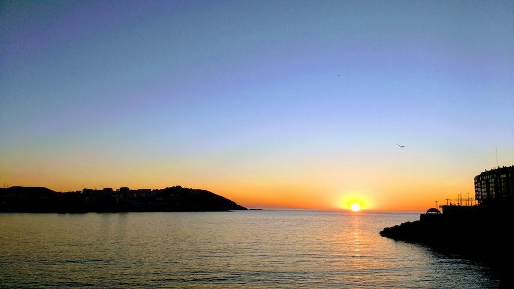 calm sea and mountain during sunrise