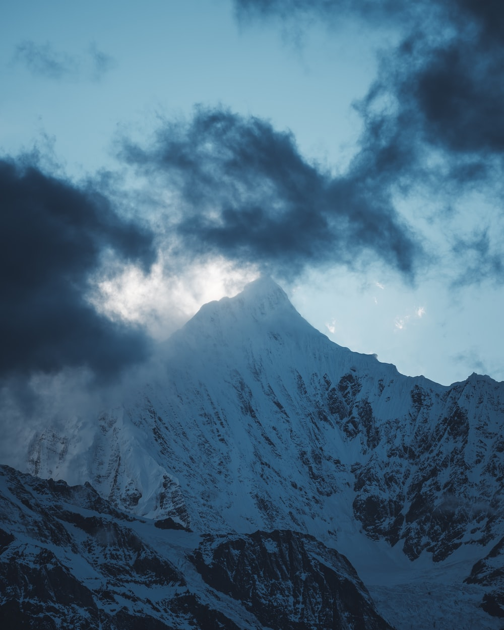 snow-covered mountain under gray clouds at daytime