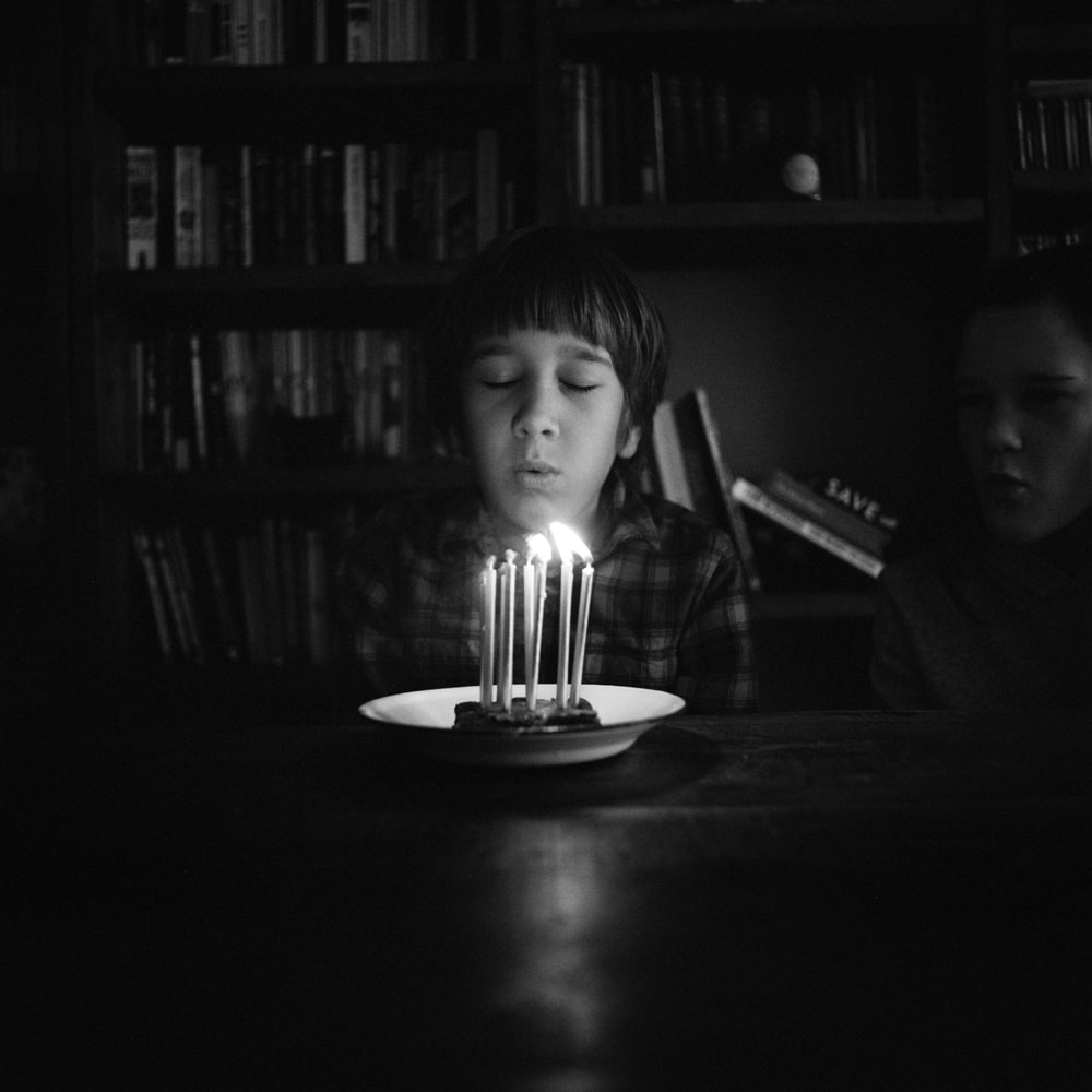 boy sitting near table and about to blow birthday candles