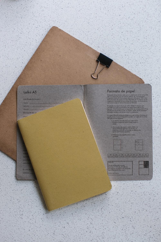 yellow softbound book on grey printer paper