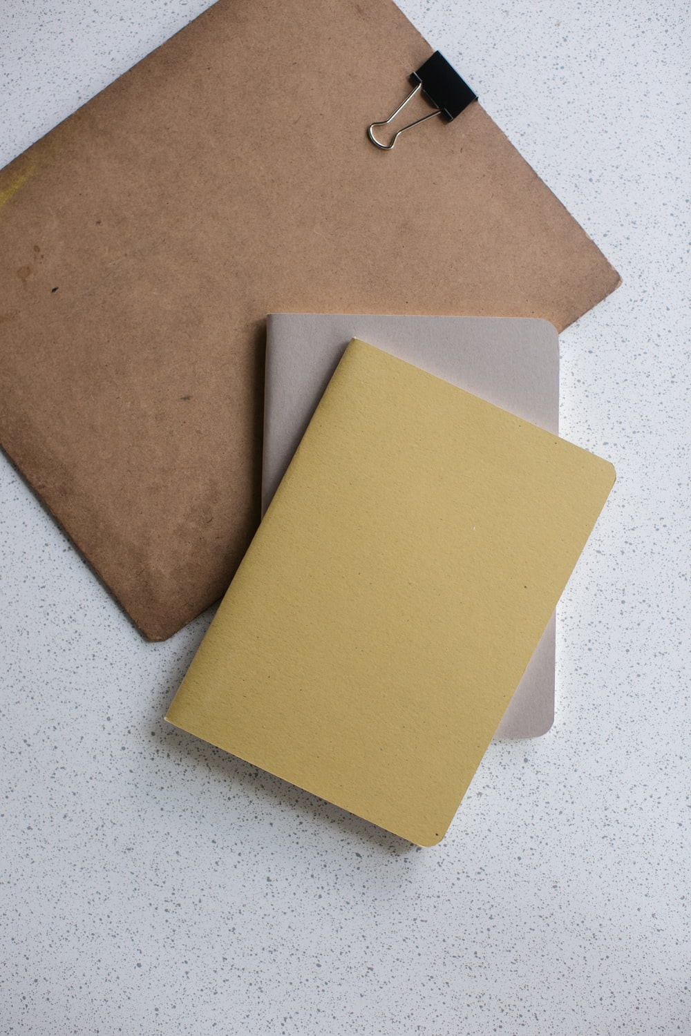yellow and gray softbound book near brown clip board