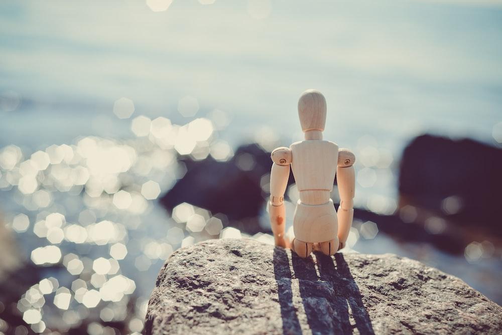 brown wooden marionette on grey rock