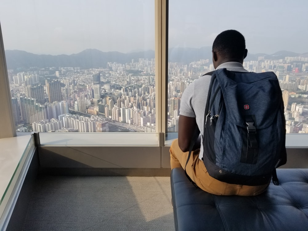 man sitting on sofa with blue backpack watching city during daytime