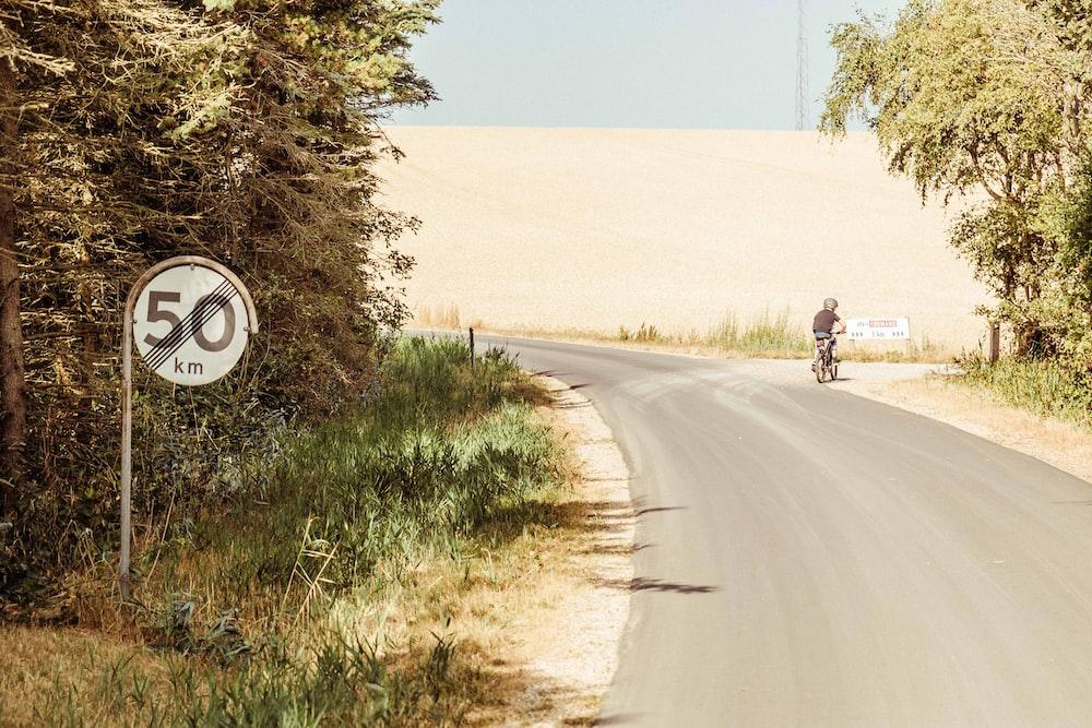 person riding bike near road