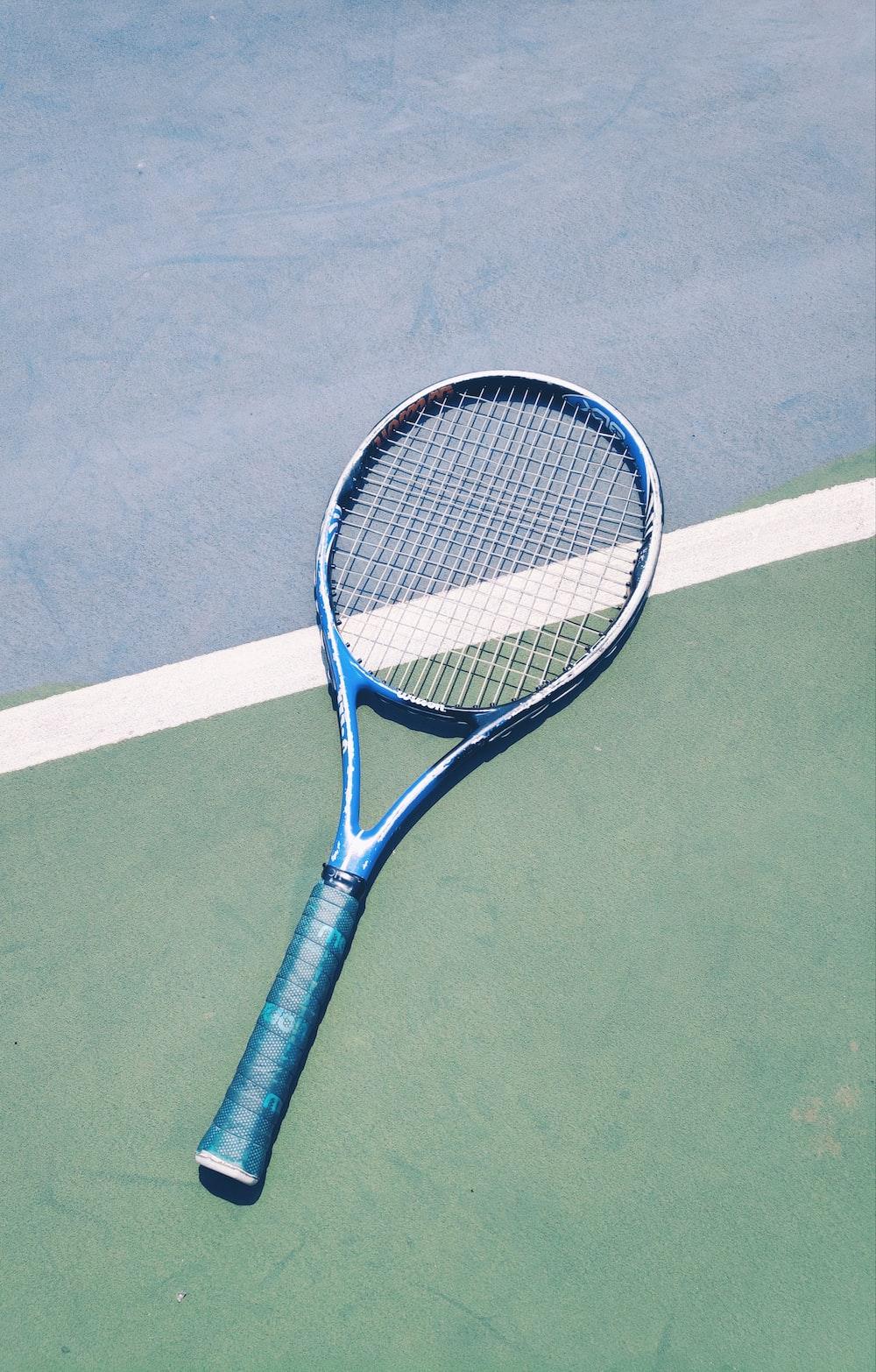 blue tennis racket on green surface