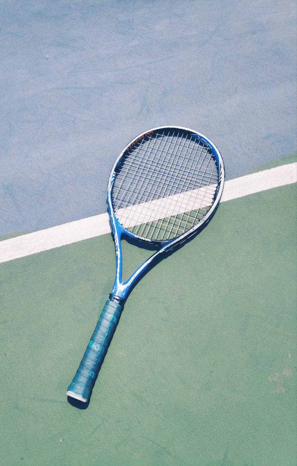 blue tennis racket on green surface