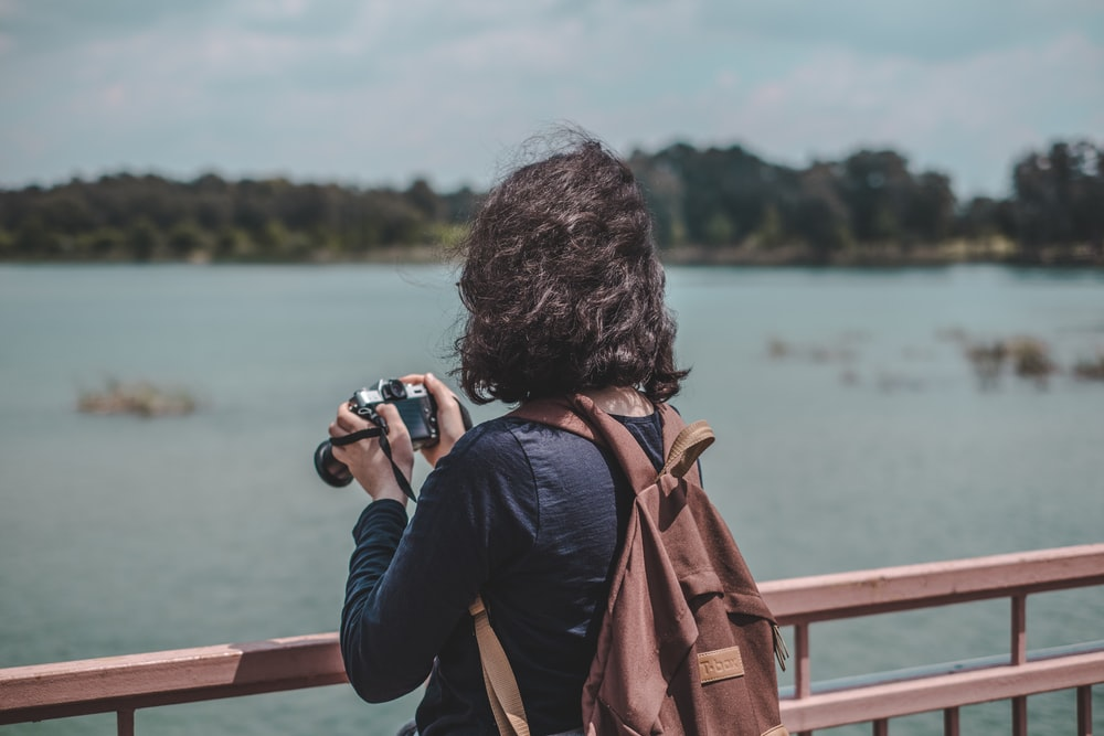 woman wearing black shirt and brown backpack holding camera standing near railings near body of water