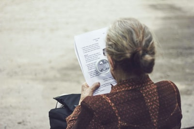 Reading woman in brown top reading paper