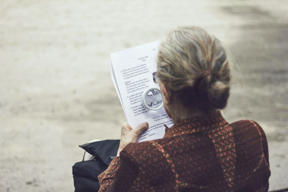 woman in brown top reading paper