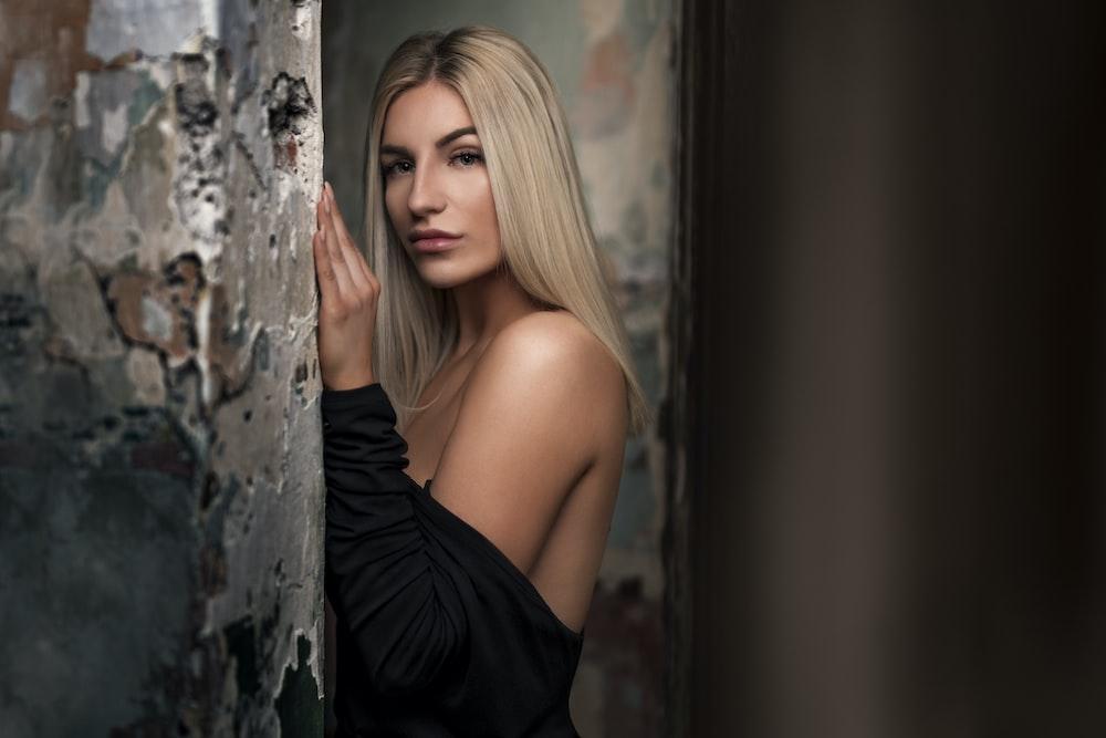 woman in black top facing gray wall