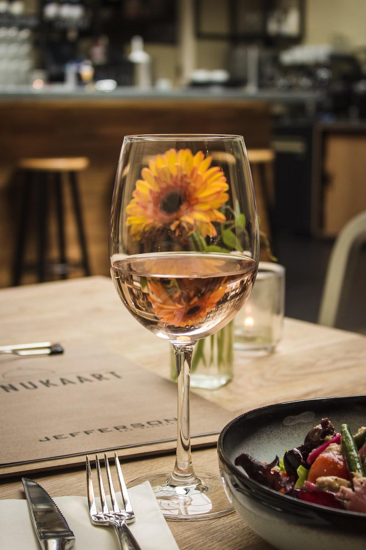 white wine on glass near gray stainless steel fork and knife beside orange gerbera daisy flower on table