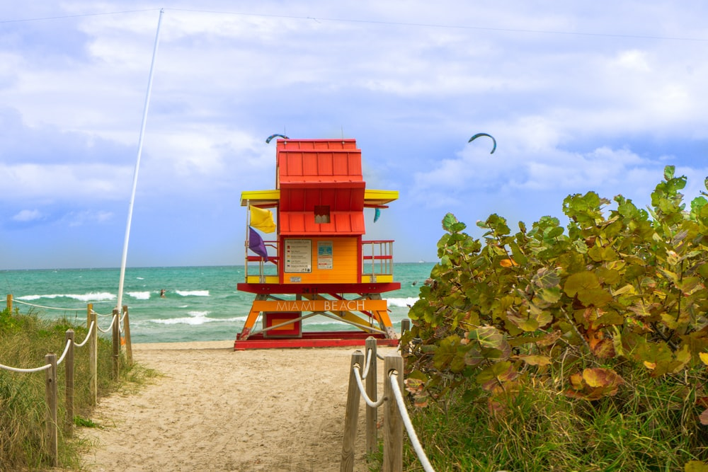 red and yellow lifeguard house in beach during daytime