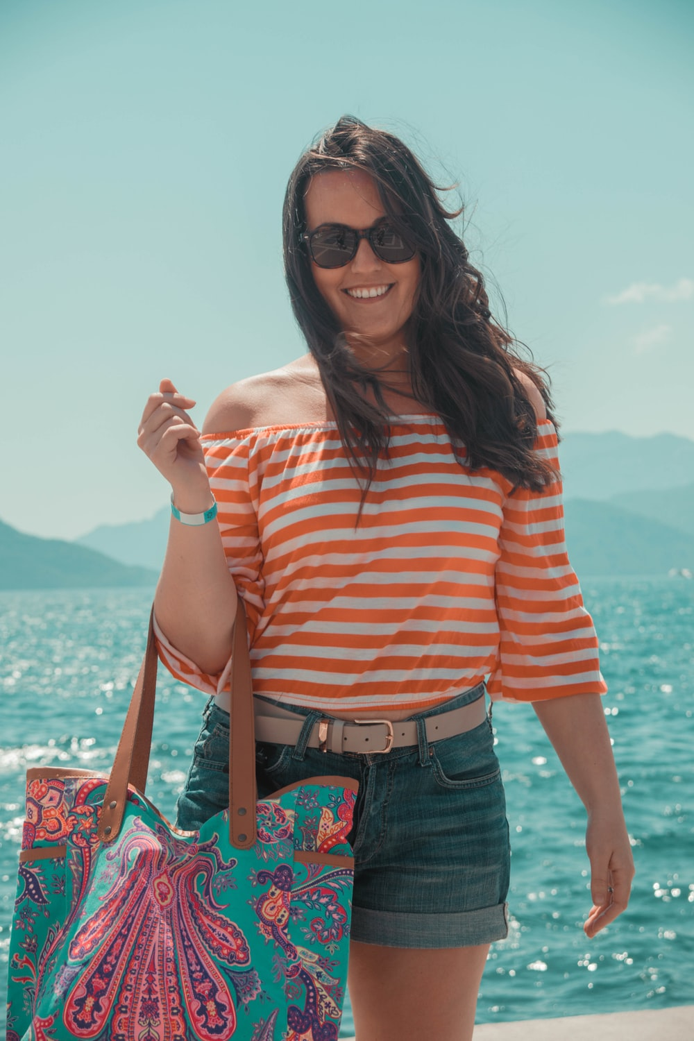 woman in striped off-shoulder top carrying blue bag