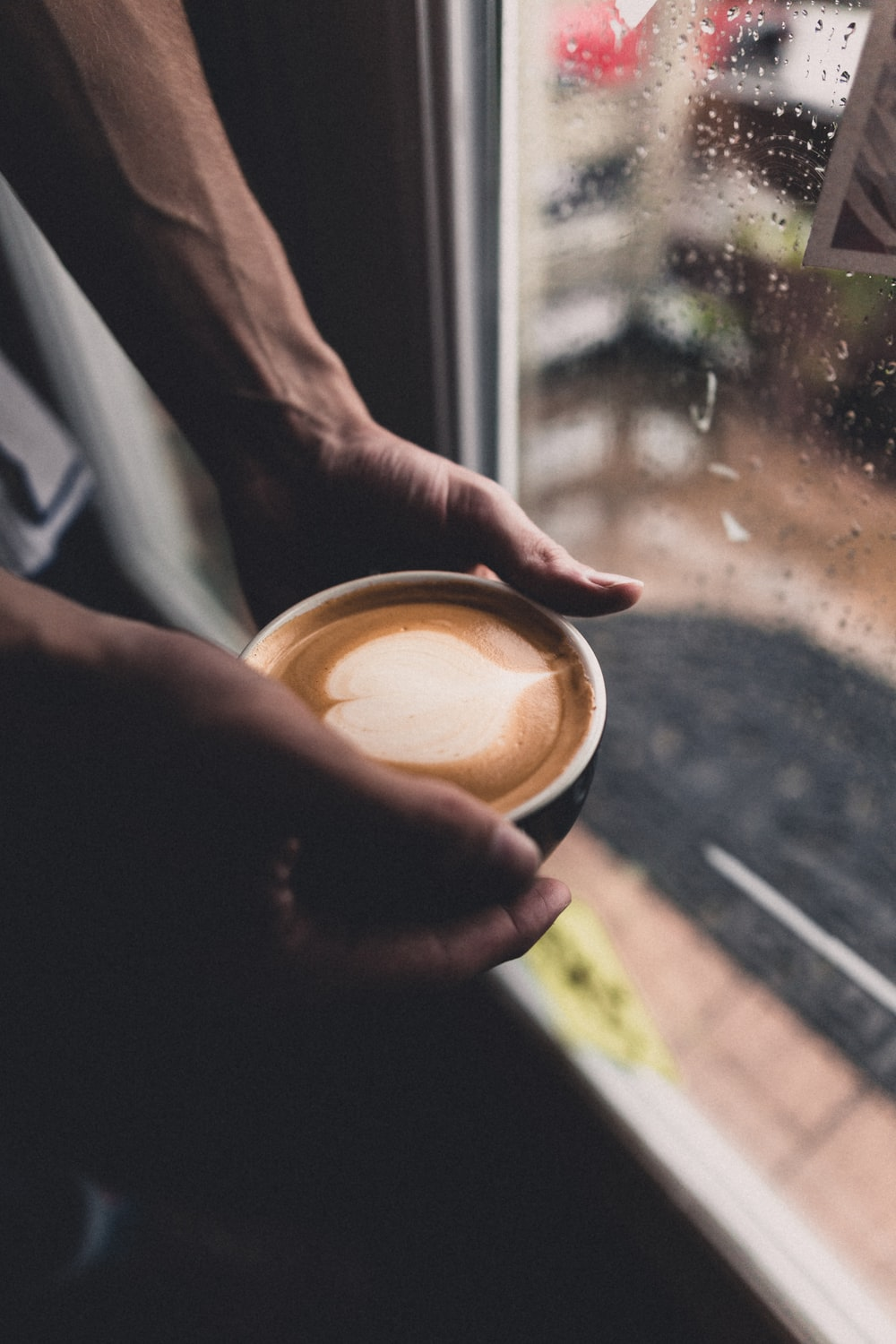 person holding cup with coffee beside glass window