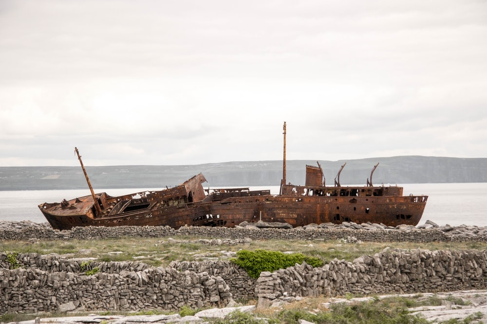 destroyed brown boat near seashore during daytime