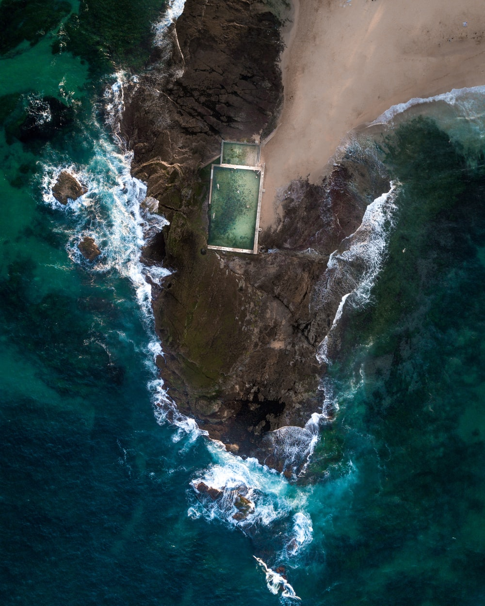 aerial photo of rock formations near sea during daytime
