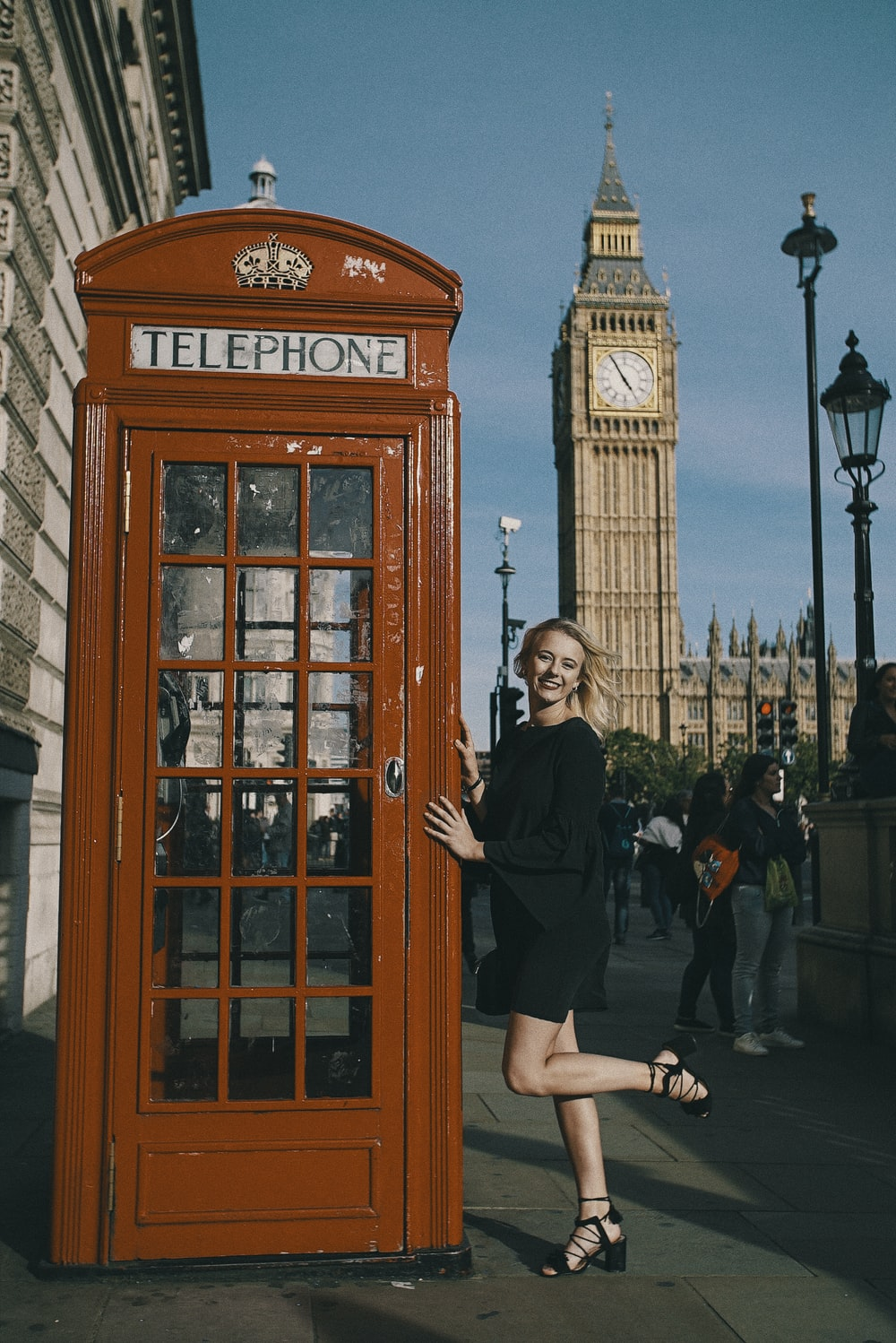 woman posing beside telephone booth with Big Ben at the back