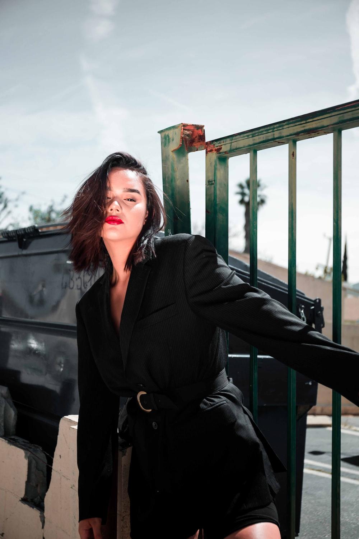 woman wearing black blazer holding grey fence