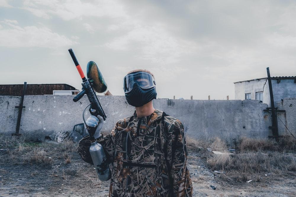 man wearing mask holding paintball gun during daytime