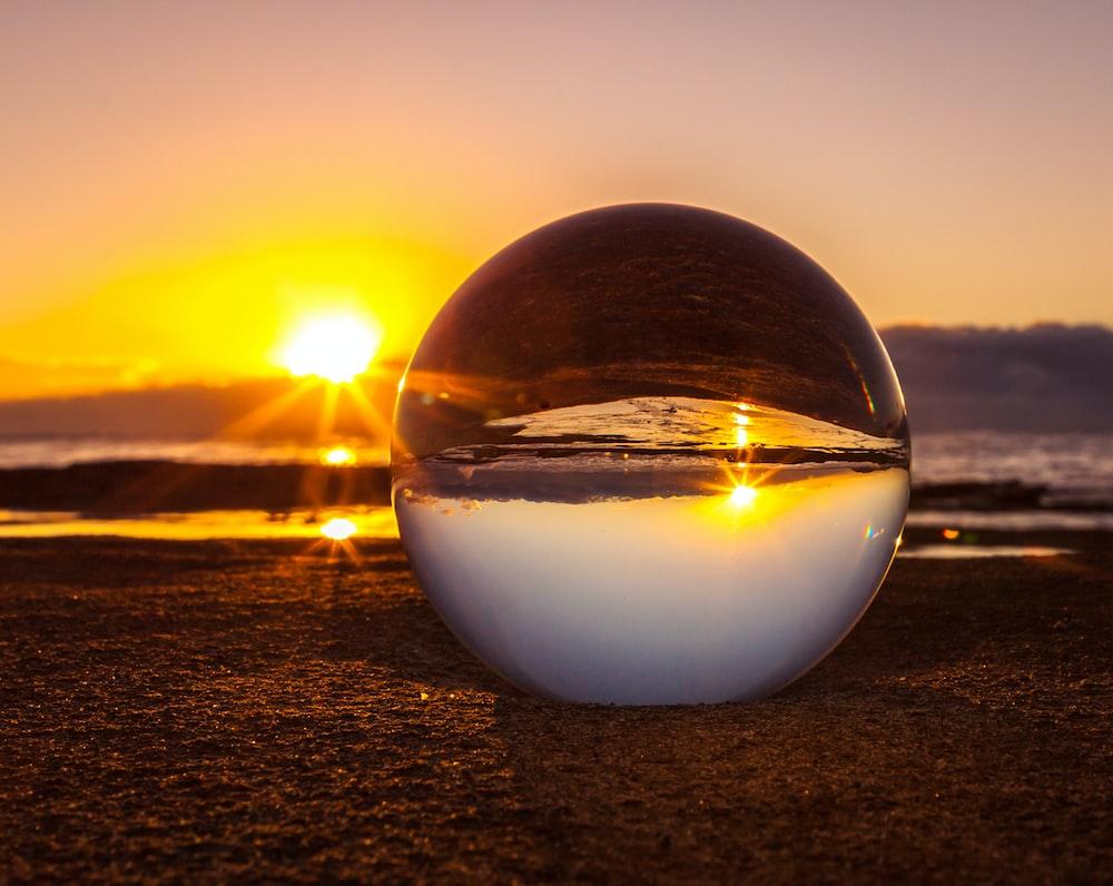 clear marble ball near seashore